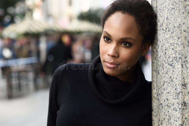 Junge schwarze Frau mit der Afrofrisur, die im städtischen backgrou steht stockfoto