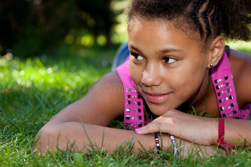 Junge schwarze Jugendliche, die auf dem Gras liegt stockbild