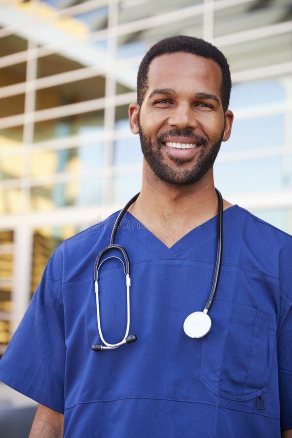 Junge schwarze männliche Gesundheitswesenarbeitskraft, die draußen, vertikal lächelt lizenzfreies stockbild