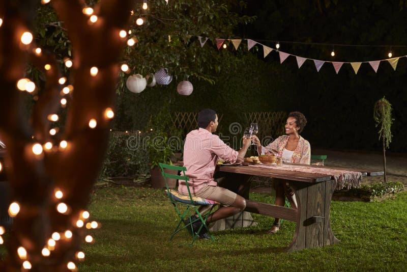 Junge schwarze Paare machen einen Toast am Abendessen in einem Garten stockfotografie