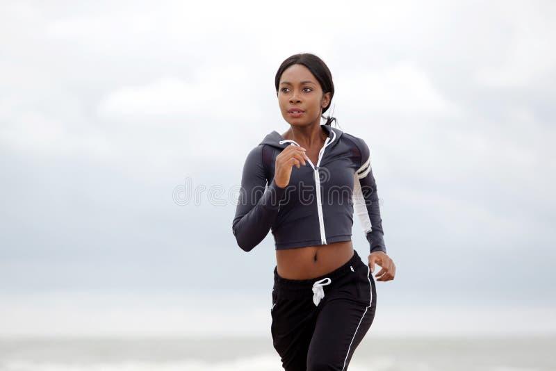 Junge schwarze Sportfrau, die draußen am Strand läuft lizenzfreie stockfotografie