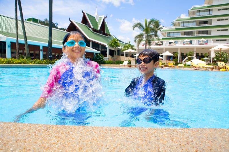 Junge Schwester und ihr Bruder im Swimmingpool lizenzfreies stockbild