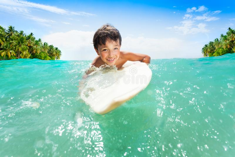 Junge schwimmt auf dem surfenden Brett in den Meereswellen stockfoto