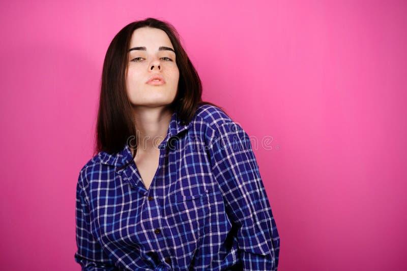 Junge selbstbewusste Frau auf einem rosa Hintergrund lizenzfreie stockbilder