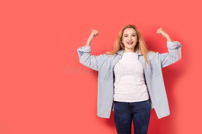 Junge selbstbewusste Frau auf einem roten Hintergrund lizenzfreie stockfotografie