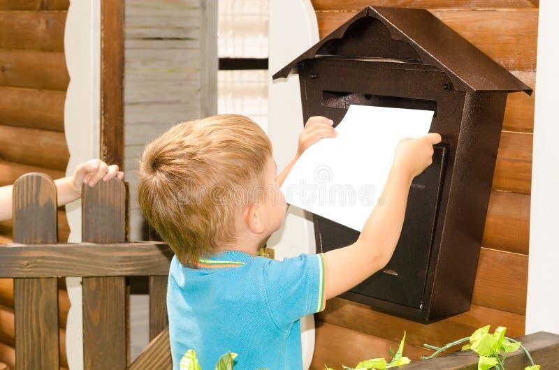 Junge sendet einen Brief stockbild