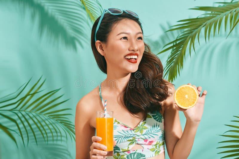 Junge sexy asiatische Frau in den Minidenimkurzen hosen geschmackvollen Saft auf Sommerzeit trinkend lizenzfreie stockfotografie