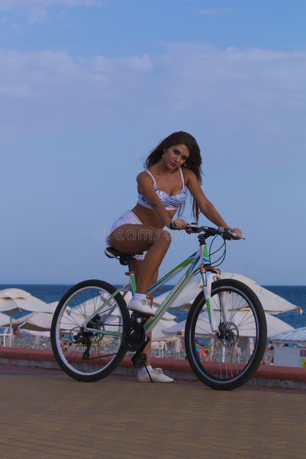 Junge sexy Frau auf dem Sportfahrrad, das auf der Straße gegen das Meer aufwirft und haben Spaß im heißen Sommer lizenzfreie stockfotografie