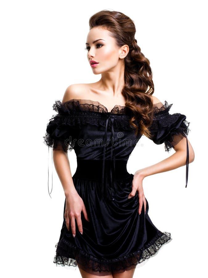 Junge sexy Frau im schwarzen Kleid, das am Studio auf weißem Hintergrund aufwirft lizenzfreies stockfoto