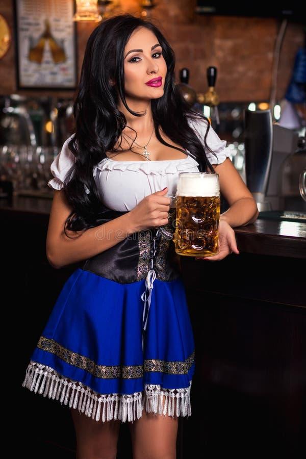 Junge sexy Oktoberfest-Kellnerin, ein traditionelles bayerisches Kleid tragend, dienender großer Bierkrug stockbilder