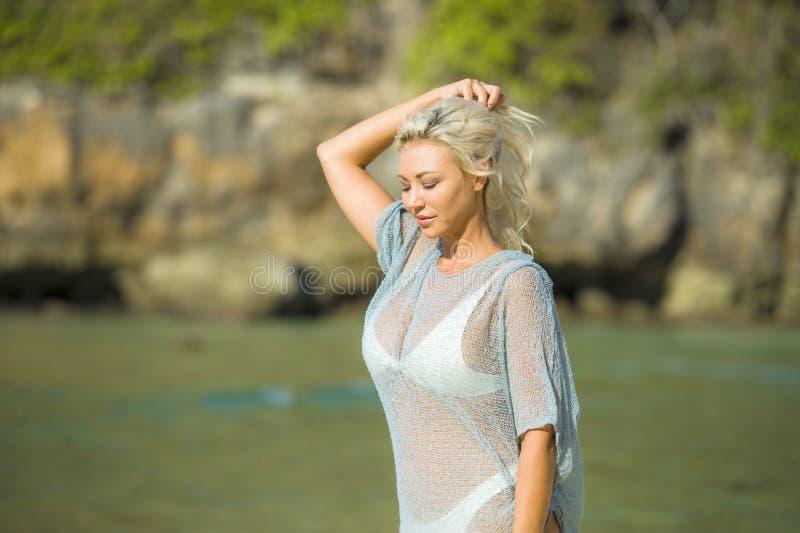 Junge sexy und glückliche blonde Frau mit dem Gehen des blonden Haares entspannt und träumerisch am schönen tropischen Paradiesst lizenzfreies stockbild