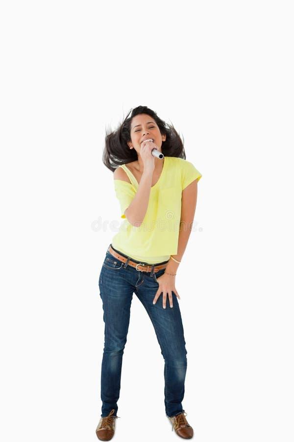 Junge singende Studentin beim Rütteln ihres Kopfes lizenzfreies stockfoto