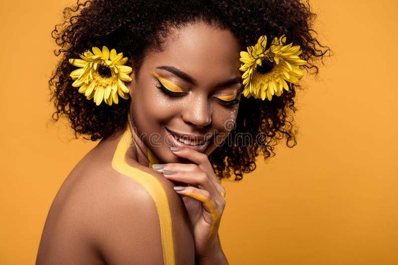 Junge sinnliche Afroamerikanerfrau mit künstlerischem Make-up und Gerberas im Haar lizenzfreies stockfoto
