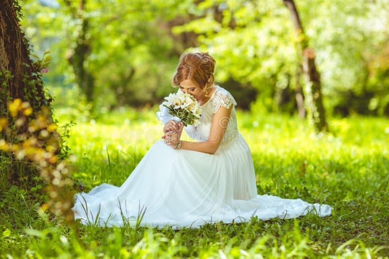 Junge sinnliche Braut, die in einem Sommer sitzt stockbild