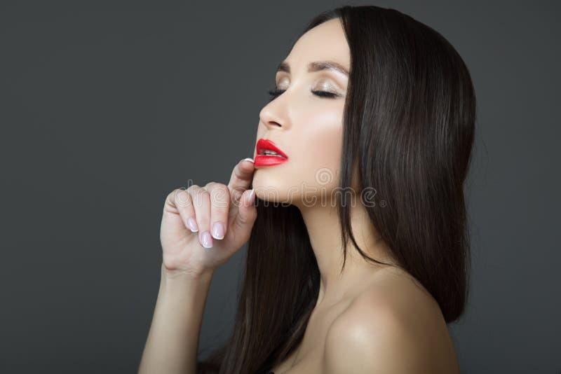 Junge sinnliche Frau mit rotem Lippenstift und dem geraden Haar Augen geschlossen Dunkler Hintergrund lizenzfreies stockbild