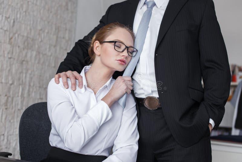 Junge sinnliche Geschäftsfrau, die Chef durch Krawatte hält lizenzfreies stockbild