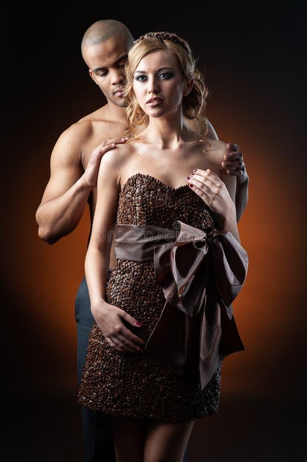 Junge sinnliche kaukasische Frau im Kleid hergestellt von der Stellung der Kaffeebohnen und des schwarzen Mannes über orange Hint lizenzfreies stockbild