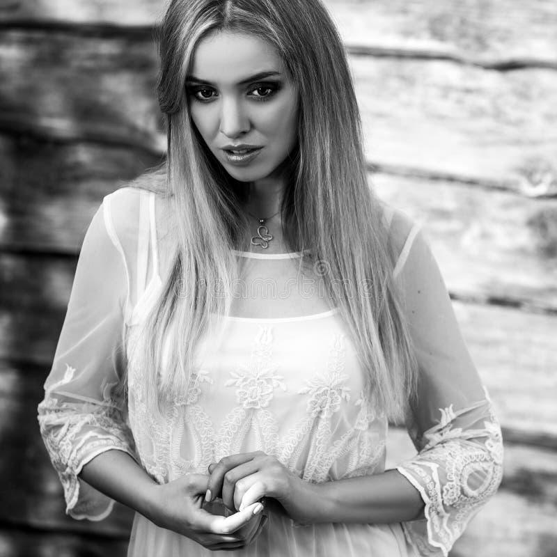 Junge sinnliche u. Schönheitsblondinehaltung auf hölzernem Hintergrund Schwarz-weißes Foto stockfoto