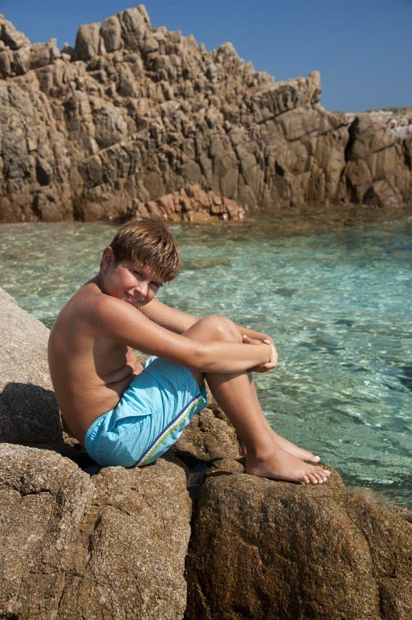 Junge sitted auf den Klippen von Cala Corsara in Spargi stockfoto