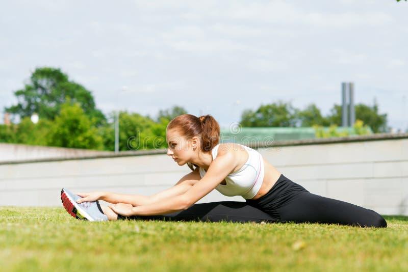 Junge, Sitz und sportliche Frau, die in den Park ausdehnen Des Sports, städtischen und gesunden Lebensstilkonzept der Eignung, lizenzfreie stockfotografie