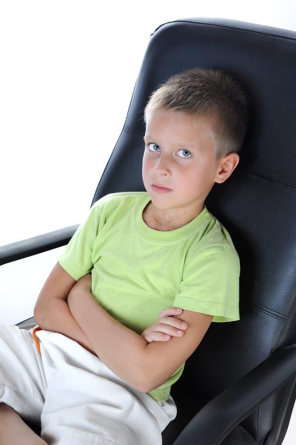 Junge sitzen auf Stuhl und betrachten Kamera lizenzfreie stockfotografie