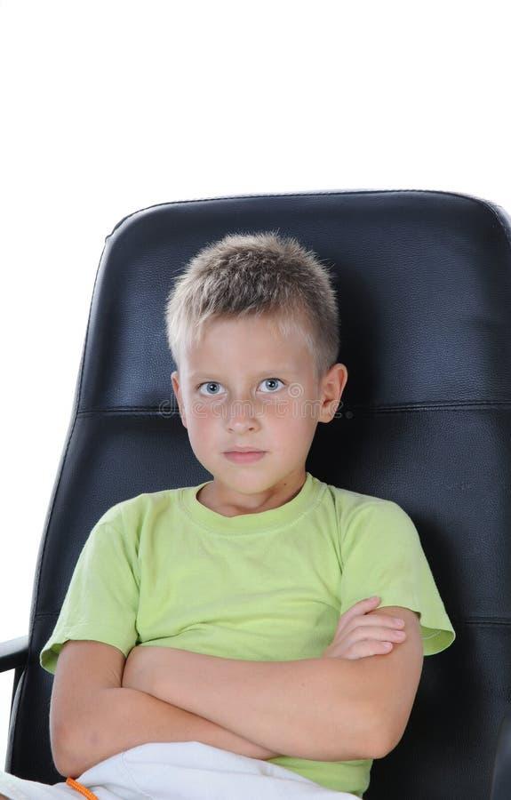 Junge sitzen auf Stuhl und betrachten Kamera stockfoto