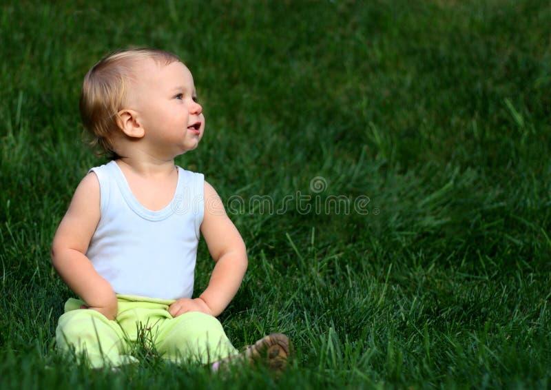 Junge sitzt auf einem Gras stockbild