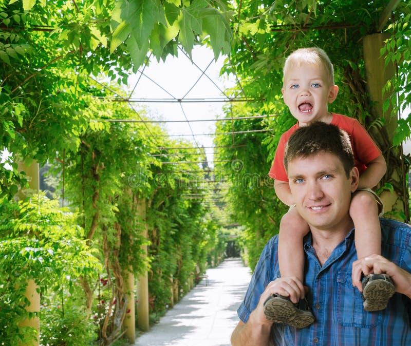 Junge sitzt auf Schulter neben Vater lizenzfreie stockfotografie