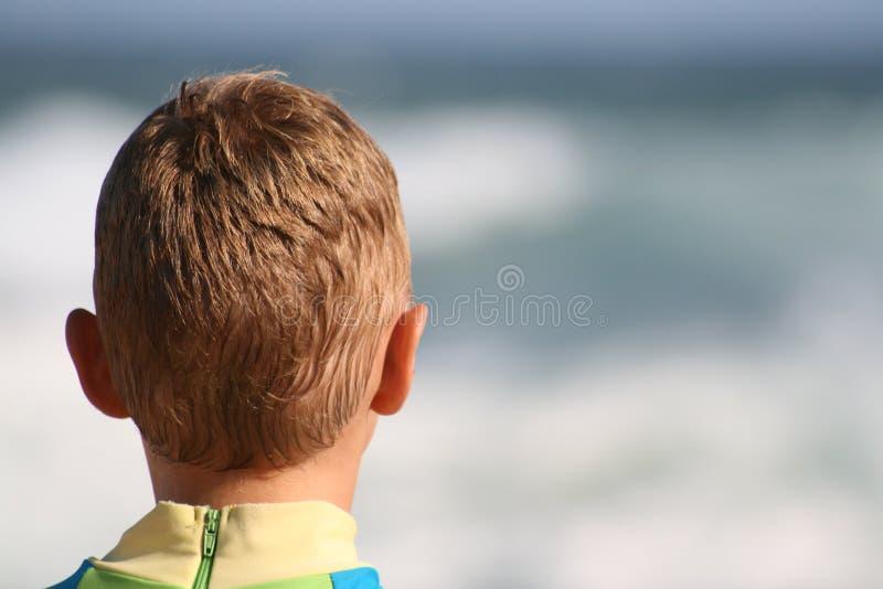 Junge sitzt auf Strand lizenzfreie stockfotos