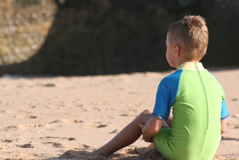 Junge sitzt auf Strand stockfoto