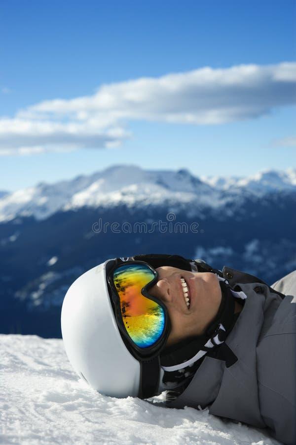 Junge Snowboarder, der auf Berg liegt. lizenzfreie stockbilder