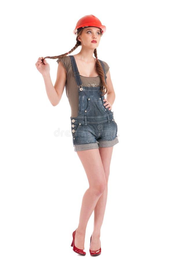 Junge spielerische Arbeitskraftfrau im Overall und im Sturzhelm lizenzfreie stockfotos