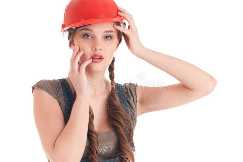 Junge spielerische Arbeitskraftfrau im Overall und im Sturzhelm lizenzfreie stockbilder