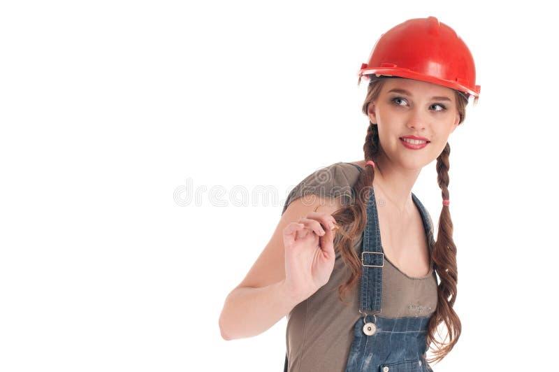 Junge spielerische Arbeitskraftfrau im Overall und im Sturzhelm lizenzfreie stockfotografie