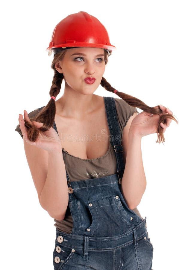 Junge spielerische Arbeitskraftfrau im Overall und im Sturzhelm stockfoto