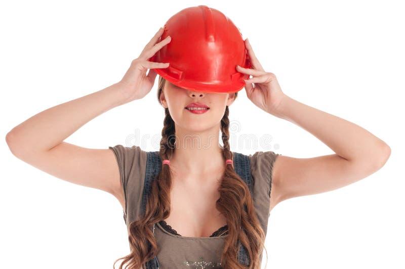 Junge spielerische Arbeitskraftfrau im Overall und im Sturzhelm stockbilder