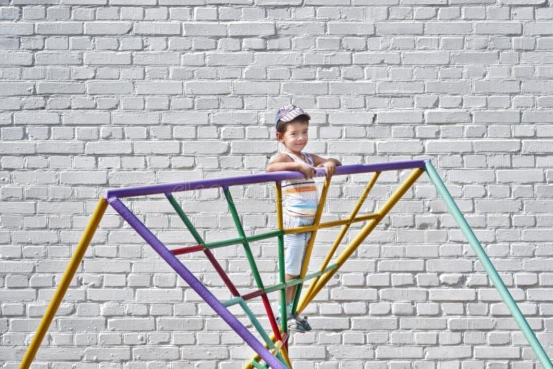 Junge am Spielplatz nahe der Backsteinmauer lizenzfreie stockfotografie