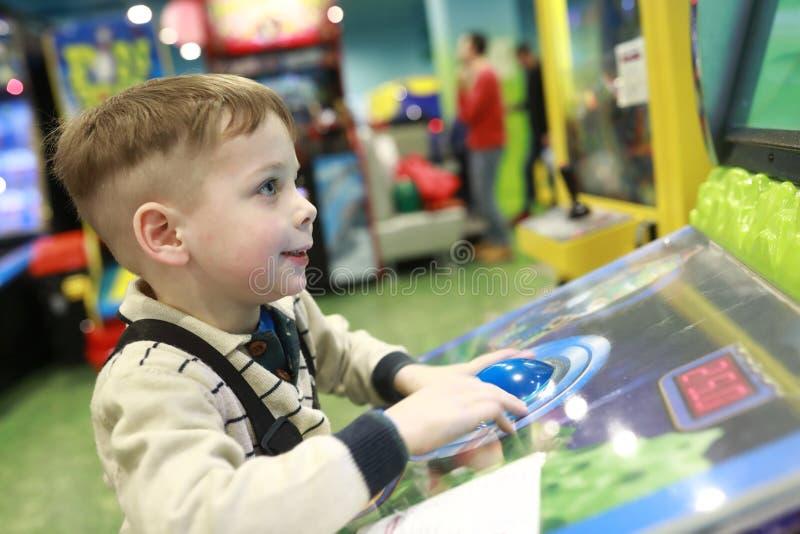 Junge spielt Arcade-Spiel stockfotos