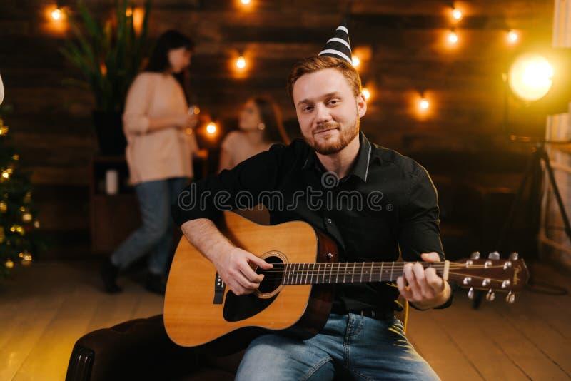Junge Junge spielt Gitarre Guy sieht glücklich und sorglos aus lizenzfreie stockfotografie