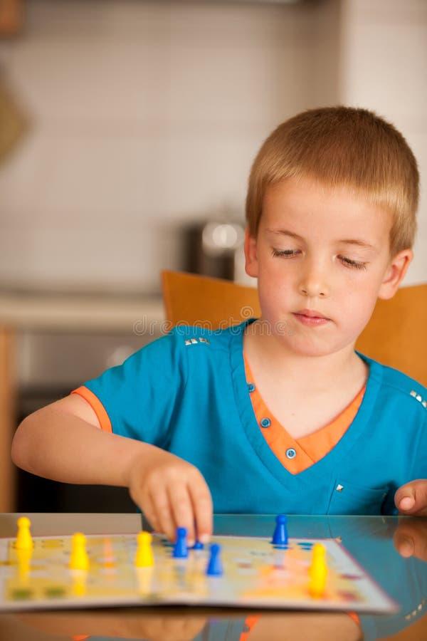 Junge spielt Ludo-Spiel auf einer Tabelle im Wohnzimmer stockfotos