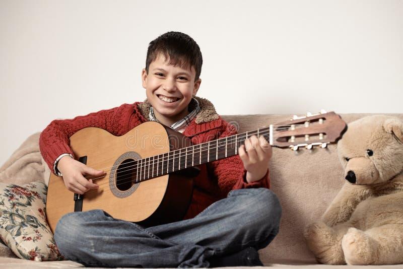 Junge spielt mit einer Akustikgitarre, sitzt auf dem Sofa mit einem Bärnspielzeug stockbild