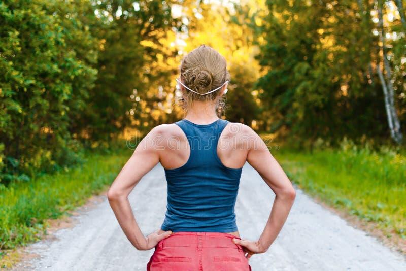 Junge Sportfrau bleibt auf der Straße stockbilder