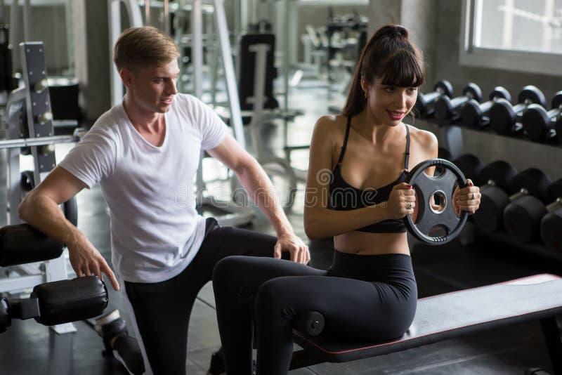 junge Sportfrau das Übungs, diehandeln sitzt, ups auf die Bank mit persönlichem Trainer in der Eignungsturnhalle Muskulöses Mädch lizenzfreie stockbilder