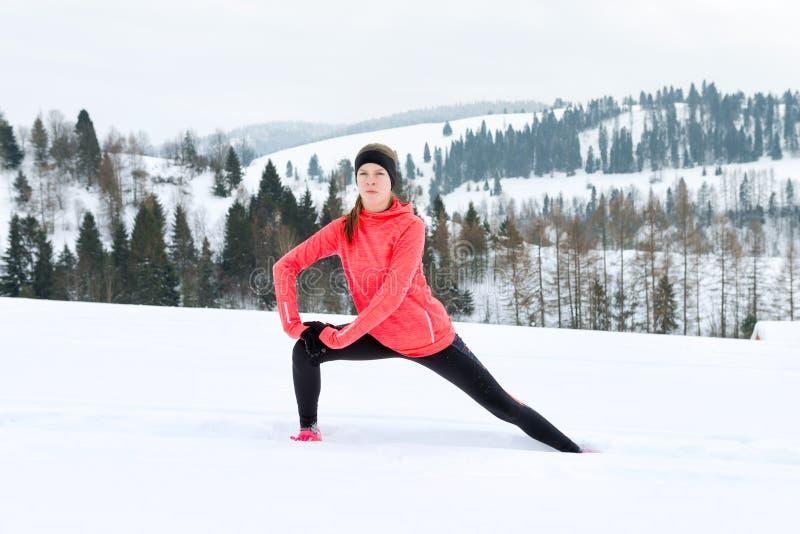 Junge Sportfrau, die Übungen während der Wintertrainingsaußenseite in den Winterbergen tragen warme Kleidungshandschuhe tut lizenzfreies stockbild
