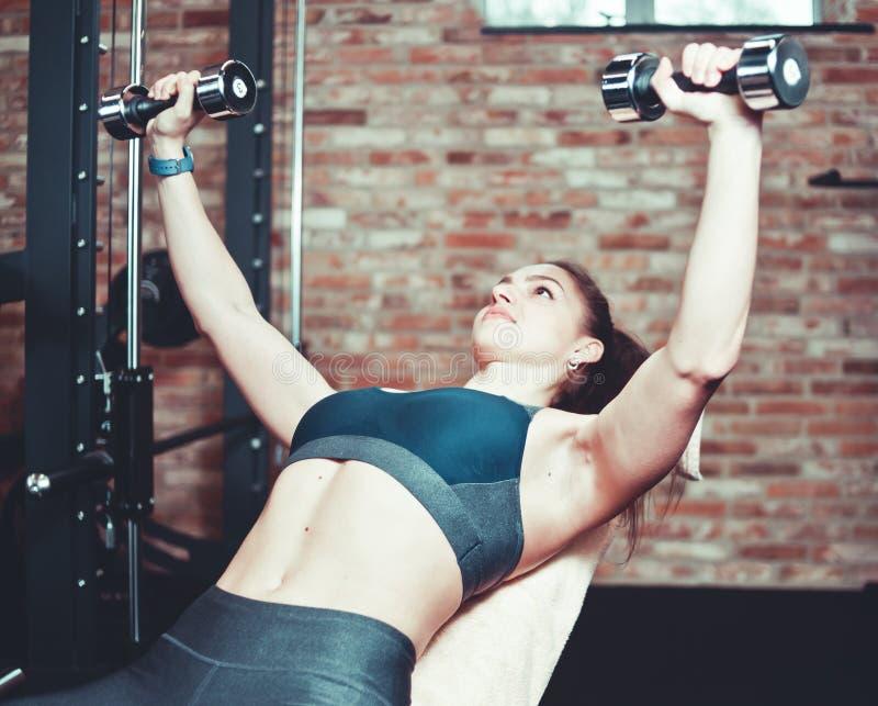 Junge Sportfrau, die Übungen mit Dummköpfen tut lizenzfreies stockfoto