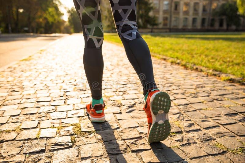 Junge Sportfrau, die Übungen während des Trainings draußen im Stadtpark tut Eignungsmodelllaufen im Freien stockfoto