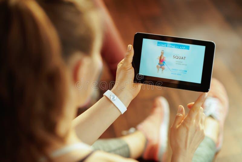 Junge Sportfrau, die Haupttrainingstrainer App im Tablet-PC verwendet lizenzfreie stockfotografie