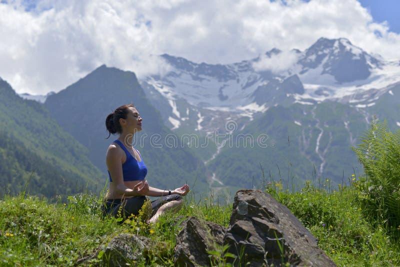 Junge Sportfrau, die Yoga auf dem grünen Gras im Sommer tut stockfoto