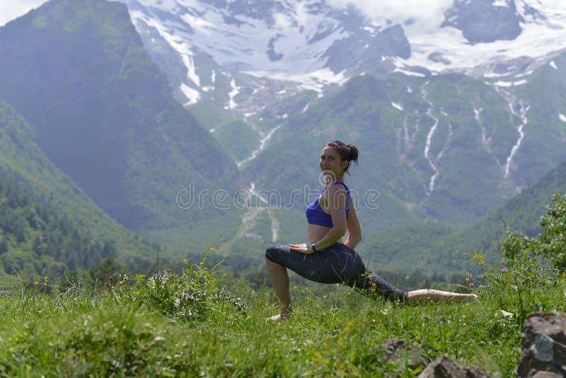 Junge Sportfrau, die Yoga auf dem grünen Gras im Sommer tut stockbild