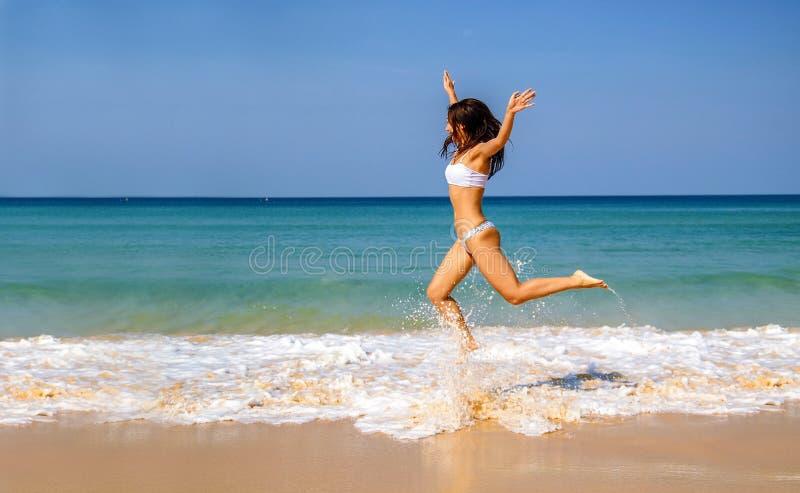 Junge Sportfrau im weißen Bikini, der auf den Strand springt stockfotos
